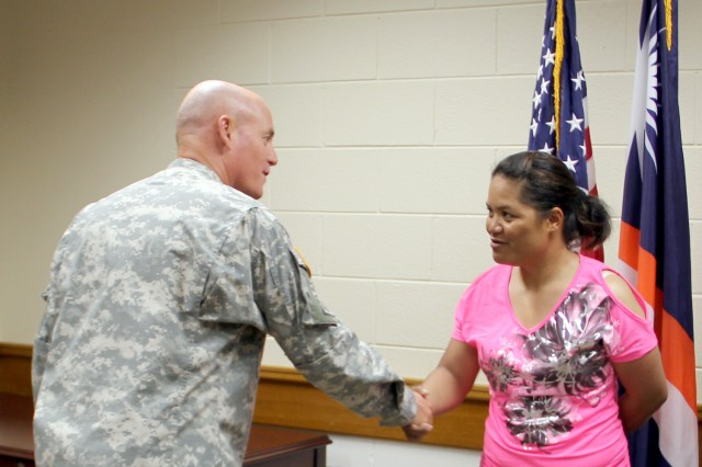 Sgt. Maj. Hohn Wolf gives a USAKA Commander's Coin to Spc. Elmita Anjain at the USAKA command center. Anjain grew up on Ebeye and Majuro and joined the U.S. Army in 2005.