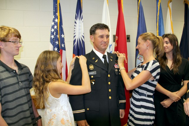 Catherine, right, and Josie Cornett pin shoulder bars to Travis Cornett's jacket to symbolize his promotion to lieutenant colonel. Cornett's daughter Logan and son Gabe watch.
