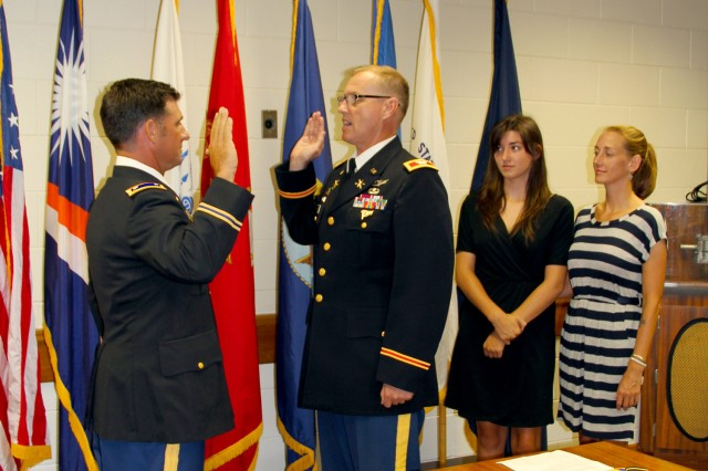 USAKA/RTS Commander Col. Joseph Gaines administers the oath of office to Lt. Col. Travis Cornett after he was promoted May 1. Cornett's wife Cathy and daughter Logan look on.