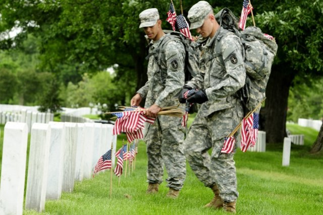 Pvt. Aaron Johnson, 3d U.S. Infantry Regiment (The Old Guard), places a small American flag in front of a grave at Arlington National Cemetery May 24.