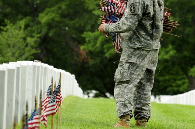 A 3d U.S. Infantry Regiment (The Old Guard) Soldier places an American flag in front of a fallen veteran's grave at  Arlington National Cemetery May 24 as part of Flag's In for Memoiral Day.