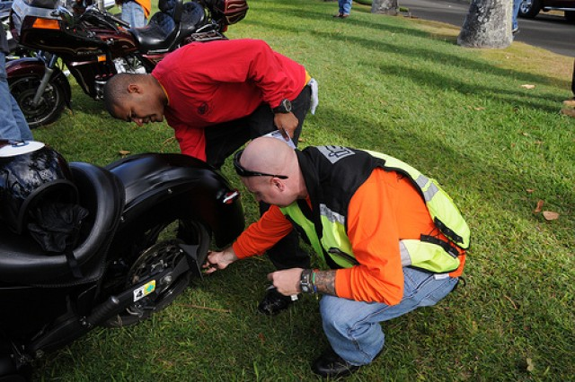 """1st  Sgt.  Hector Medina (left) from the Engineer Battalion inspects Staff Sgt. Norman Stentz, U.S. Army Pacific driver motorcycle May 24 prior to the 80-mile """"Memorial Day Ride for the Fallen""""."""