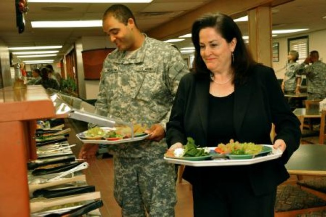 Katherine Hammack (right), assistant secretary of the Army for installations, energy and environment, accompanied by Army Pvt. Calvin McCollon from Chicago, carries her lunch to a table at the Camp Bullis dining facility. Hammack was visiting Joint Base San Antonio May 21-22 to tour installations on Fort Sam Houston and Camp Bullis, and discuss world-wide and future energy and environmental initiatives for the Army.