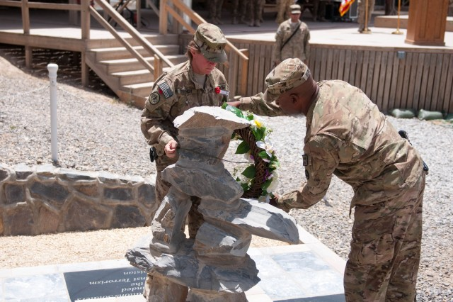 Brig. Gen. Kristin K. French, the commanding general of the 3d Sustainment Command (Expeditionary), and Command Sgt. Maj. Karl Roberts, the 3d ESC's senior enlisted leader, place a wreath honoring fallen heroes during Kandahar Airfield's Memorial Day observance on May 28. (U.S. Army photo by Staff Sgt. Michael Behlin)