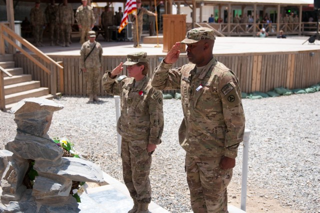 Brig. Gen. Kristin K. French, the commanding general of the 3d Sustainment Command (Expeditionary), and Command Sgt. Maj. Karl Roberts, the 3d ESC's senior enlisted leader, salute a memorial honoring fallen heroes during Kandahar Airfield's Memorial Day observance on May 28. (U.S. Army photo by Staff Sgt. Michael Behlin)