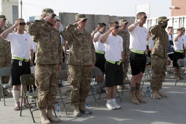 Service members and wounded warriors salute as the National Anthem is sung during the NATO Multinational Role 3 Medical Unit Memorial Day ceremony on May 28, 2012 at Kandahar, Afghanistan. More than 150 service members and wounded warriors attended the ceremony in remembrance of those who've served in any war conflict. (U.S. Army photo by Sgt. Gregory Williams)