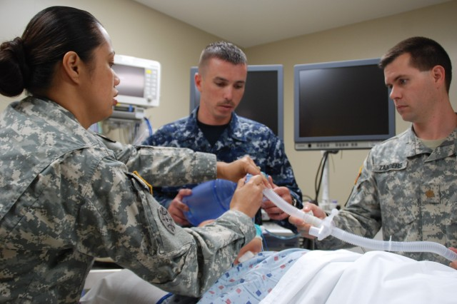 Staff Sgt. Easter Jackson, clinical instructor, explains the functions of a transport ventilator to Navy Petty Officer 2nd Class Justin Speight, an Interservice Respiratory Therapy Program student, as Maj. Thomas Zanders, the program's medical director, looks on in the Pulmonary Department at San Antonio Military Medical Center, May 23, 2012.