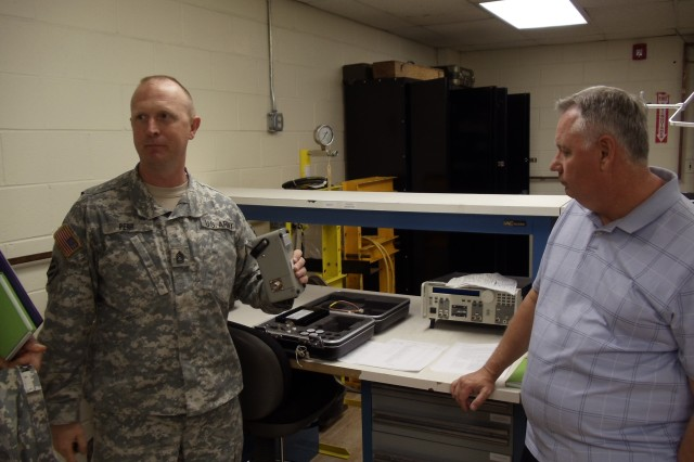 FORT STEWART, Ga. (April 13, 2012) -  SFC Matthew Perr, 632nd Support Maintenance Company, shares TMDE insights and recommendations with Dale Taylor, Chief, Maintenance / Reset Branch, FORSCOM G-4.