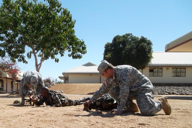 Instructors from the U.S. Army Security Assistance Training Management Organization, help Namibian soldiers with the proper low crawl technique during the Small Unit Tactics portion of the Warrior Leader Instructor Training Course.  USASATMO's Engagement Branch Mobile Training Team conducted a Warrior Leader Instructor Course there as part of establishing a Namibian Noncommissioned officer training course.