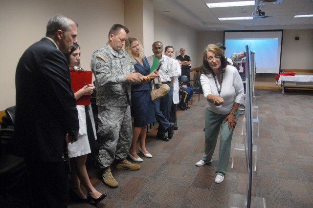 Microbiologist Rebecca Smiley, with the department of clinical investigations, presents a medical research poster to a panel of judges during the May 16 Research Day at William Beaumont Army Medical Center.