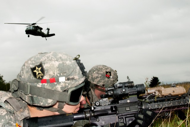 Soldiers take cover after exiting a UH-60 Blackhawk during an air insertion training exercise here, May 22. Companies from 2nd Battalion, 158th Assault Helicopter Battalion partnered with A Co., 2nd Battalion, 23rd Infantry Regiment, delivering the infantry Soldiers to the landing zone, about one mile from their objective.