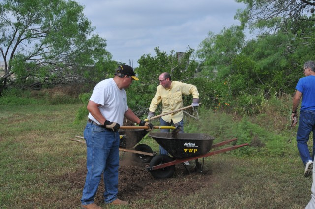 Randy Cerar and Kevin Lariscy, U.S. Army Environmental Command, load mulch at a recent Cleanup event.  U.S. Army Environmental Command teamed up with the San Antonio Parks and Recreation Department and other member organizations at Joint Base San Antonio to mulch trees and thin out invasive, non-native plant species from the park.