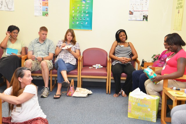 Members of a CRDAMC Pregnancy Centering Program exchange gifts at the group's baby shower May 29. Kristyn Leftridge (back, left), Centering program coordinator, said a baby shower is one of many activities offered by the program that help moms-to-be bond and gain support from one another. (U.S. Army photo by Patricia Deal, CRDAMC Public Affairs)