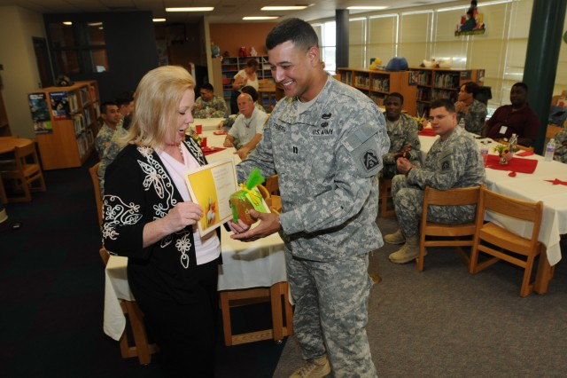 SAN ANTONIO - Kathleen St. Claire, the principal at John J. Pershing Elementary School, presents a certificate of appreciation to Capt. Eduardo Figueroa, commander, Headquarters Support Company, Headquarters and Headquarters Battalion, U.S. Army North, during a luncheon for volunteers May 23 in the school's library. Figueroa, along with his fellow volunteers from Army North, mentor and tutor children at the school once a week as part of Fort Sam Houston's Adopt-a-School program. (U.S. Army photo by Staff Sgt. Keith Anderson, Army North PAO)