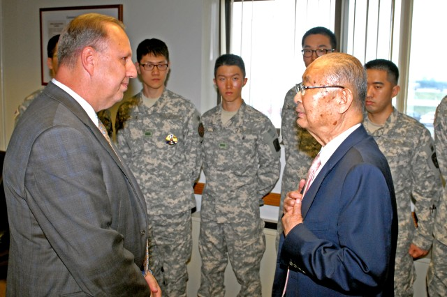 Retired Republic of Korea Army Gen. Paik, Sun-yup (right) visits with Mark Cox, United States Army Garrison Humphreys deputy commander, during a visit to post. In the background are Korean Augmentation to the United States Army (KATUSA) Soldiers, who also got a chance to meet Paik, the first four-star general in Korean history.