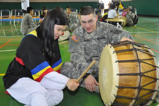 Pvt. Seth Wilson from 14th Military Police Detachment, 94th MP Battalion gets a lesson about Samulnori, Korea's traditional percussion music, from a Yangseo High School student in Kyeonggi-do, May 25.  -U.S. Army photo by Cpl. Choi Sung-il