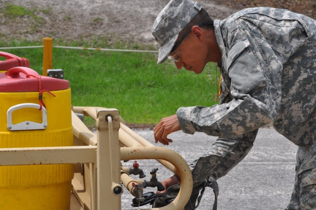Spc. Daud Aliahmad, Company A, 2nd Battalion, 13th Infantry Regiment, fills up his hydration system after returning from the firing lane Tuesday. Soldiers in Basic Combat Training are monitored for their water intake to avoid heat injuries in the hot summer temperatures on Fort Jackson.