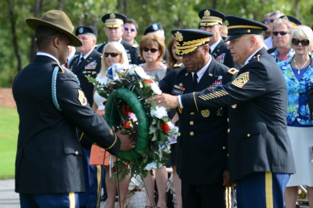 Brig. Gen. Bryan Roberts, center, and Post Command Sgt. Maj. Kevin Benson, right, lay a wreath in remembrance of the nation's fallen service members.