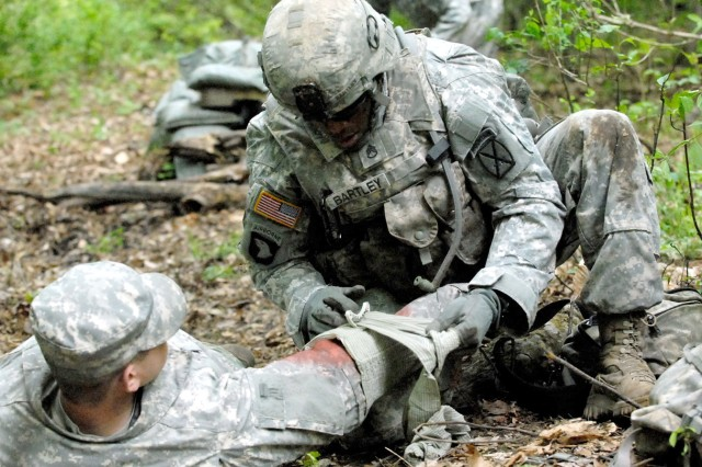 Staff Sgt. Devaughn D. Bartley applies an Israeli emergency bandage to the arm of a simulated casualty during an Expert Infantryman's Badge lane held May 16 on Fort Drum. EIB testing concluded May 18 with a 12-mile foot march.