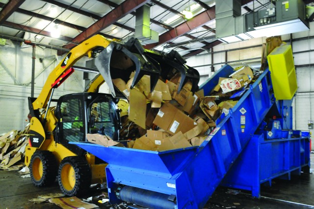 Lisa Groholski, Directorate of Public Works Recycling Center operator, operates a skid steer to transport cardboard into a recycling baler.