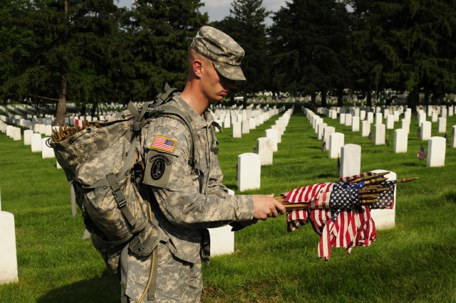 Staff Sgt. Victor Whaley, firing party commander, Charlie Company, 3d U.S. Infantry Regiment (The Old Guard), waits in front of a fallen veteran's grave stones as a Soldier walks by grabbing a bundle of American flags in Arlington National Cemetery, Va., May 24. Each year for the past 40 years, the 3d U.S. Infantry Regiment has honored America's fallen heroes by placing American flags before the gravestones and niches of service members buried at both Arlington National Cemetery and the U.S. Soldier's and Airmen's Home National Cemetery just prior to Memorial Day weekend. (U.S. Army Photo by Sgt. Luisito Brooks)