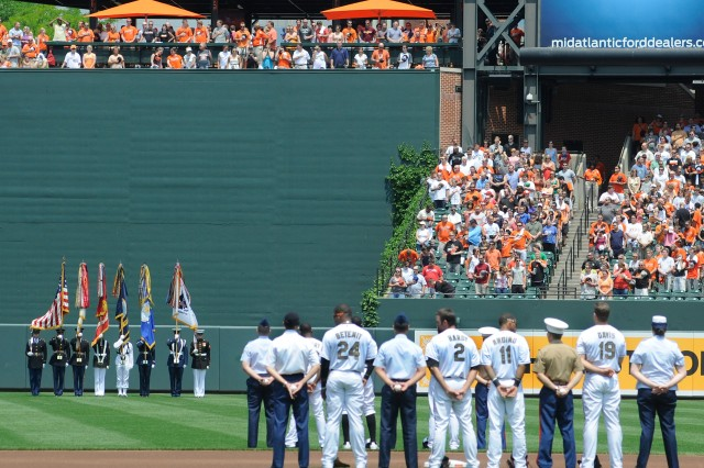 The Military District of Washington Armed Forces Color Guard stands in the outfield for the National Anthem, as nine Fort Meade service members join the Baltimore Orioles starting lineup on the field at Oriole Park at Camden Yards on Sunday for the team's Military Appreciation Day. Fort Meade participated in pregame events including throwing the opening pitch.