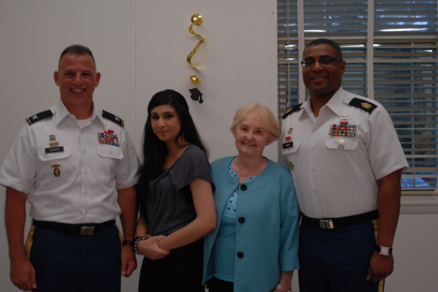 Garrison Commander Col. Edward C. Rothstein, Garrison Command Sgt. Maj. Charles E. Smith and Evelyn Silva, volunteer coordinator for the Enlisted Spouses Club, congratulate Kinza Shah, 17, a Meade High School senior, as the recipient of the ESC's Evelyn Silva Scholarship For Excellence on May 21 at Argonne Hills Chapel Center.