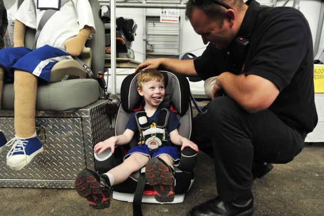 Mark T. Oakley, of the Fort Meade Fire Department, greets 3-year-old Brian Volochenko as he sits in a child passenger safety seat during the installation's annual Safety, Health and Wellness Expo. The four-hour event featured interactive activities to encourage vehicle and motorcycle safety, as well as free blood pressure and body fat percentage screenings.