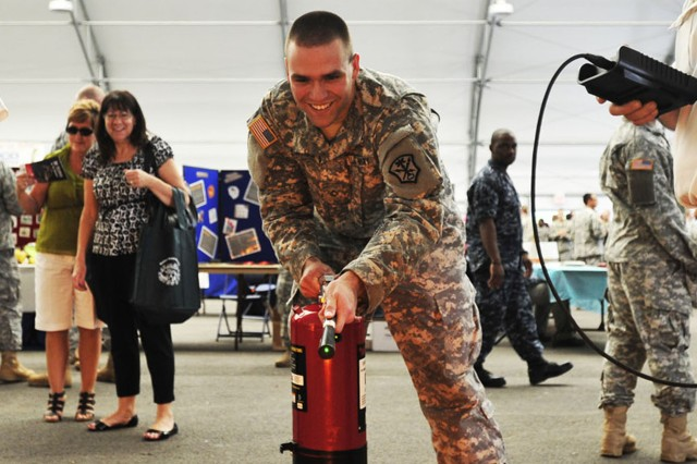 Pfc. Alexander Davison, 781st Military Intelligence Battalion, extinguishes a mock fire during the Safety, Health and Wellness Expo sponsored May 24 at the Pavilion by the Installation Safety Office.