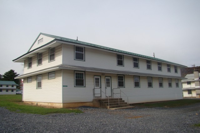 The newly restored Area 13 features historic block structures and a series of 21 WWII-era wooden barracks like this one. Faced with a need for modern meeting space, barracks, and MWR areas, the PAARNG began planning to tear down the district and build anew at a cost of several million dollars. The wooden barracks, which are still being used as living quarters, were upgraded to enhance living conditions and energy efficiency. Installing cleaner energy systems has reduced energy costs for the barracks by 40% to 50%.