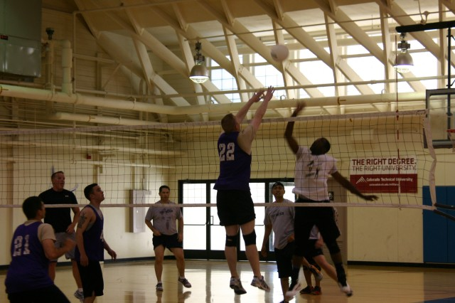 Chris Carter of the 704th Military Intelligence Brigade tries to block 707th Communications Squadron's Henry Schott's spike during the intramural volleyball championship May 24 at Murphy Field House. The 707th defeated the 704th: 25-21, 19-25 and 15-12.