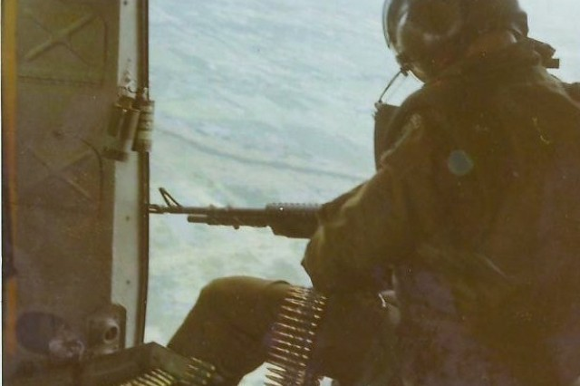 """Spec 4 Robert """"Pinky"""" Pilkinton sits in the Huey's door gunner position in September 1971 while flying over the Mekong Delta, Vietnam. This picture was taken just before he got shot down for the third time in Vietnam."""