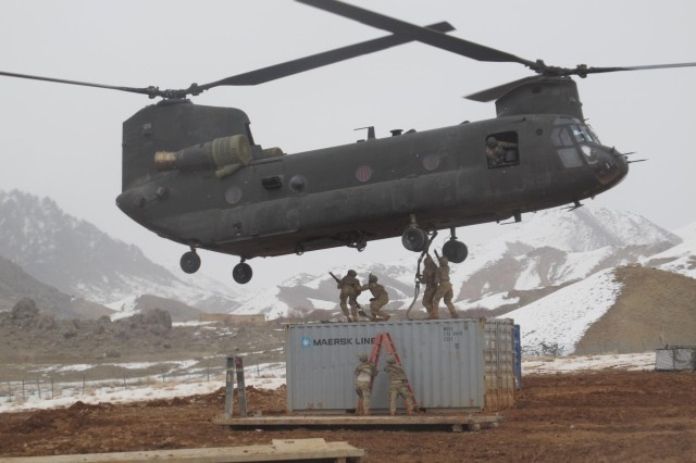 A CH-47 Chinook helicopter assigned to 3rd Battalion, 25th Aviation Regiment, 25th Combat Aviation Brigade, hovers while being hooked up to a container for a sling load resupply mission at a remote outpost in Afghanistan, March 3, 2012.