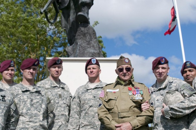 World War II and D-Day veteran, John Perozzi, 82nd Airborne Division, takes a picture with active duty 82nd Abn. Div. Soldiers in front of the Iron Mike statue after a ceremony that commemorated the La Fiere, Ste. Mere Eglise, France, World War II and D-Day events, June 3, 2012. Task Force 68, which is made up of paratroopers from U.S., Germany, France, Holland, and United Kingdom, re-enacted the D-Day airborne operation on the La Fiere fields near Ste. Mere Eglise, France to commemorate the heroic acts of the WWII paratroopers who made the jump 68 years ago. After the jump, the task force marched into the town of Ste. Mere Eglise to the sounds of cheers from the locals. Task Force 68 is in Normandy, France, to commemorate the 68th anniversary of D-Day.