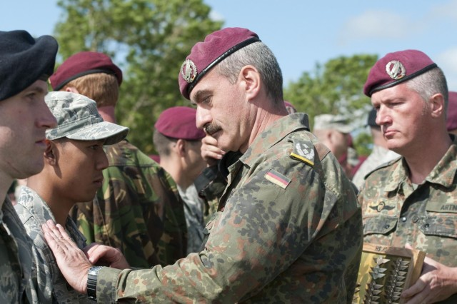 Paratroopers exchange German jump wings at La Fiere drop zone after completing an airborne operation commemorating the D-Day and World War II events, June 3, 2012. Task Force 68, which is made up of paratroopers from U.S., Germany, France, Holland, and United Kingdom, re-enacted the D-Day airborne operation on the La Fiere fields near Ste. Mere Eglise, France to commemorate the heroic acts of the WWII paratroopers who made the jump 68 years ago. After the jump, the task force marched into the town of Ste. Mere Eglise to the sounds of cheers from the locals. Task Force 68 is in Normandy, France, to commemorate the 68th anniversary of D-Day.