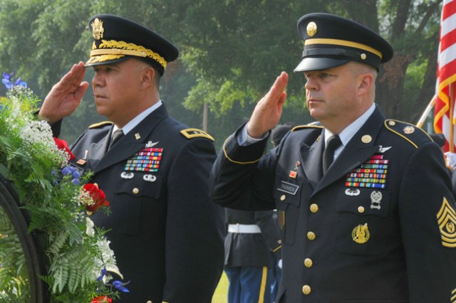 Maj. Gen. Anthony G. Crutchfield, USAACE and Fort Rucker commanding general, and Aviation Branch Command Sgt. Maj. James H. Thomson Jr. salute after placing a wreath at the Veterans Park monuments.