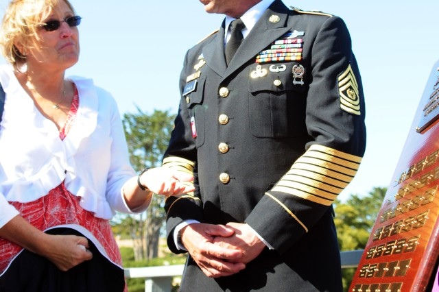 PRESIDIO OF MONTEREY, Calif. -- Following the Presidio's Memorial Day event May 24, Cynthia Pyeatt, mother of Marine Sgt. Lucas Pyeatt, speaks with Command Sgt. Maj. Pedro Ayala next to a plaque bearing the names of all DLIFLC graduates who died in overseas contingency operations. Sgt. Pyeatt was killed on Feb. 5, 2011 during combat operations in Afghanistan.