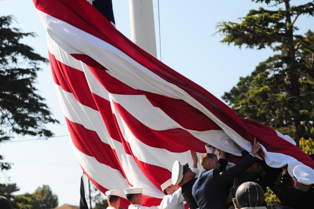 PRESIDIO OF MONTEREY, Calif. -- The ceremonial garrison flag is lowered and collected by military service members during the playing of Taps at a Memorial Day ceremony for the Defense Language Institute Foreign Language Center May 24.