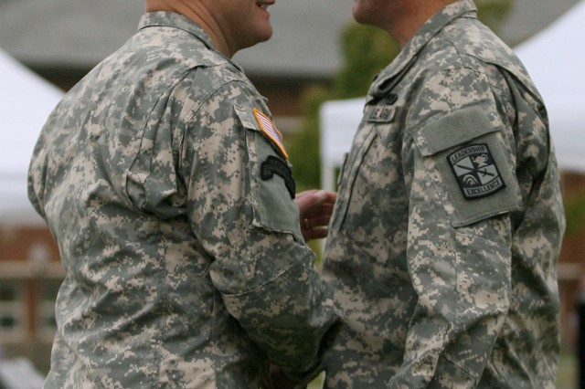 Colonel Charles Evans (left) shakes hands with Col. John Kelly, who assumes command of the 8th Brigade from Evans during today's change of command ceremony at Joint Base Lewis-McChord, Wash.