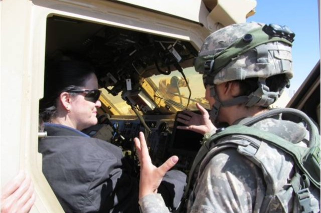 Seated inside a Command HUMVEE, the Hon. Katherine Hammack receives a brief of the power requirements and challenges of communicating across a battle space the size of Connecticut.