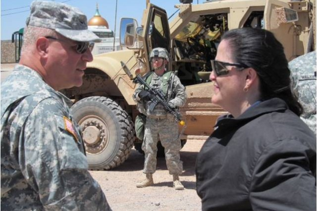 As a Soldier stands at the ready, Hon. Katherine Hammack, assistant secretary of the Army for installations, energy and environment discusses equipment being evaluated during NIE 12.1 with Col. Curtis Hudson, spokesman for the Brigade Modernization Command.