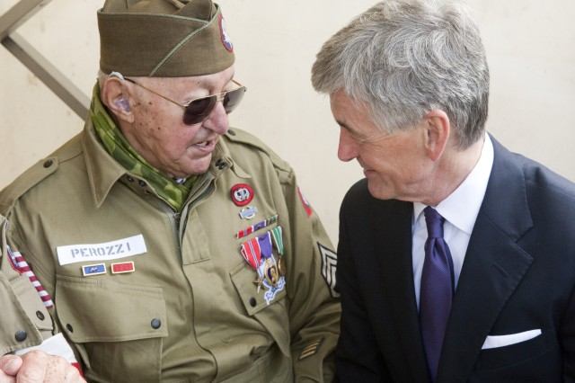 Secretary of the Army John McHugh speaks to WWII veteran John Perrozi, June 3, 2012, during a commemoration event in honor of the 68th anniversary of D-Day.  Perrozi, who was making his first trip back to France since the war, was an 82nd Airborne Division paratrooper on D-Day.  He was awarded France's highest military medal, the Légion d'Honneur, later in the day during a ceremony at the Iron Mike statue near Sainte Mere Eglise, France.