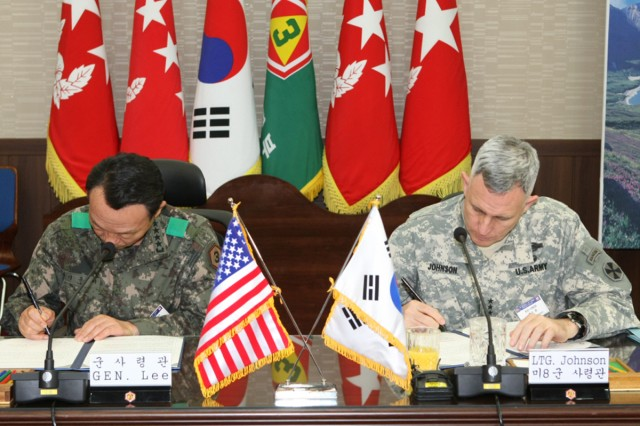 Eighth Army Commander Lt. Gen. John D. Johnson (right) signs an agreement with Gen. Lee Hong-ki, commanding general of the Third ROK Army.