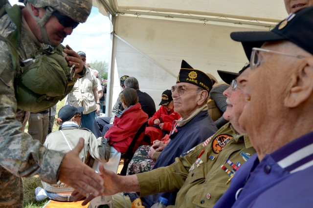 A U.S. Army paratrooper who jumped into the marshes west of Saint Mere Eglise, June 3, 2012, shakes hands with World War II veterans who fought there during the D-Day invasion.