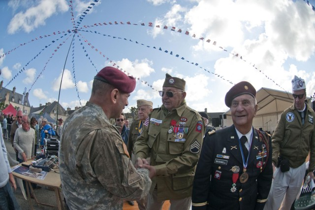 Maj. Gen. Jeffrey Jacobs, U.S. Army Civil Affiars & Psychological Operations Command (Airborne) commanding general, shakes hands with World War II and D-Day veteran, John Perozzi, 82nd Airborne Division, after a ceremony honoring him and other World War II veterans, June 3, 2012. Task Force 68, which is made up of paratroopers from U.S., Germany, France, Holland, and United Kingdom, re-enacted the D-Day airborne operation on the La Fiere fields near Ste. Mere Eglise, France to commemorate the heroic acts of the WWII paratroopers who made the jump 68 years ago. After the jump, the task force marched into the town of Ste. Mere Eglise to the sounds of cheers from the locals. Task Force 68 is in Normandy, France, to commemorate the 68th anniversary of D-Day.
