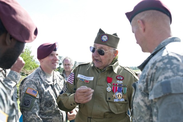 World War II and D-Day veteran, John Perozzi, 82nd Airborne Division, talks with active duty 82nd Abn. Div. Ssoldiers after a ceremony that commemorated the La Fiere, Ste. Mere Eglise, World War II and D-Day events, June 3, 2012. Task Force 68, which is made up of paratroopers from U.S., Germany, France, Holland, and United Kingdom, re-enacted the D-Day airborne operation on the La Fiere fields near Ste. Mere Eglise, France to commemorate the heroic acts of the WWII paratroopers who made the jump 68 years ago. After the jump, the task force marched into the town of Ste. Mere Eglise to the sounds of cheers from the locals. Task Force 68 is in Normandy, France, to commemorate the 68th anniversary of D-Day.