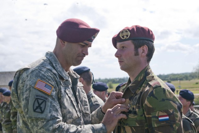 Capt. Brett Baker, U.S. Army Civil Affairs & Psychological Operations Command (Airborne), pins on U.S. jump wings onto allied forces during a wing exchange on La Fiere during a ceremony in honor of World War II and D-Day events, June 3, 2012. Task Force 68, which is made up of paratroopers from U.S., Germany, France, Holland, and United Kingdom, re-enacted the D-Day airborne operation on the La Fiere fields near Ste. Mere Eglise, France, to commemorate the heroic acts of the World War II paratroopers who made the jump 68 years ago. After the jump, the task force marched into the town of Ste. Mere Eglise to the sounds of cheers from the locals. Task Force 68 is in Normandy, France, to commemorate the 68th anniversary of D-Day.
