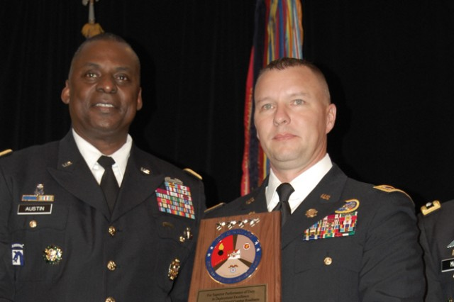General Lloyd J. Austin III (left), Army Vice Chief of Staff, presents an award to CW2 Patrick Dougherty, 159th Combat Aviation Brigade, Fort Campbell, Kentucky.  His unit won the top honor in the deployment category during the 2012  Combined Logistics Excellence Awards (CLEA) ceremony.
