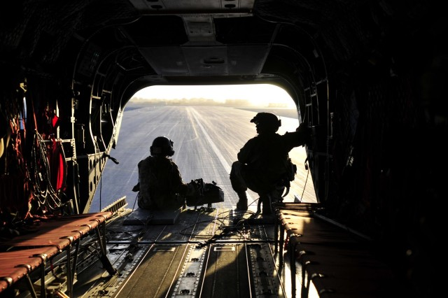 Sgt 1st Class Edward Willis (left), quality control non-commissioned officer in charge, and Sgt. 1st Class Derek Walters, flight platoon sergeant, both with Company B, 3rd Battalion, 25th Aviation Regiment, 25th Combat Aviation Brigade, keep watch out the back of a CH-47F Chinook helicopter as it prepares to take off during the early morning hours for an aircraft recovery mission on Kandahar Airfield, Afghanistan, June 3.
