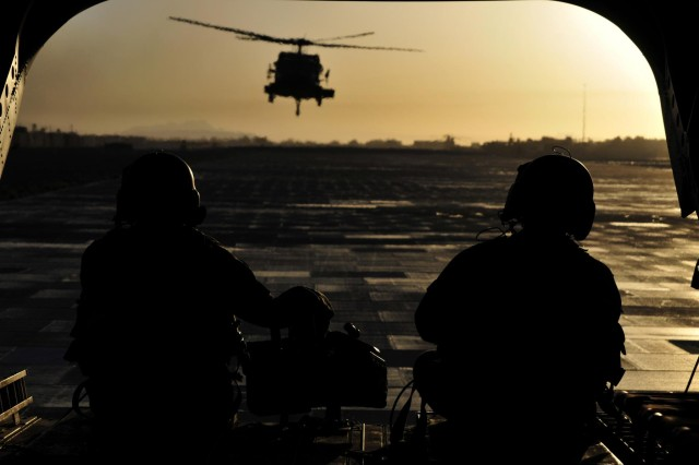 Sgt. 1st Class Edward Willis (left), quality control non-commissioned officer in charge, and Sgt. 1st Class Derek Walters, flight platoon sergeant, both with Company B, 3rd Battalion, 25th Aviation Regiment, 25th Combat Aviation Brigade, keep watch out the back of a CH-47F Chinook helicopter as it prepares to take off during the early morning hours for an aircraft recovery mission with a UH-60 Black Hawk helicopter on Kandahar Airfield, Afghanistan, June 3.